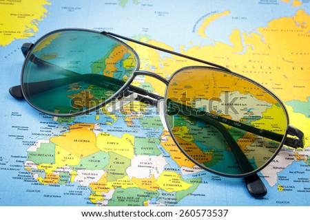 Pilot sunglasses on a world map - stock photo