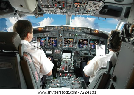 Pilots in the cockpit during a commercial flight - stock photo