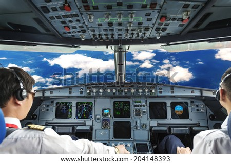 Pilots in the plane cockpit and cloudy sky - stock photo