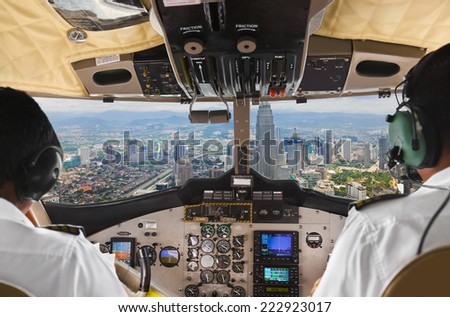 Pilots in the plane cockpit and town - stock photo
