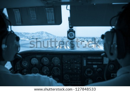Pilots in the small plane cockpit landing, color processed - stock photo