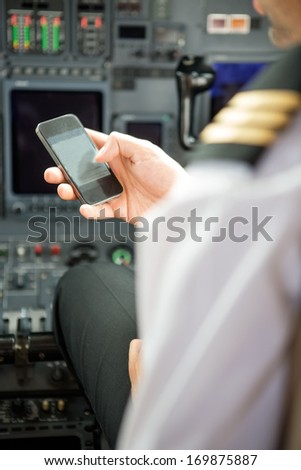 Pilots using smartphone in cockpit of private jet - stock photo