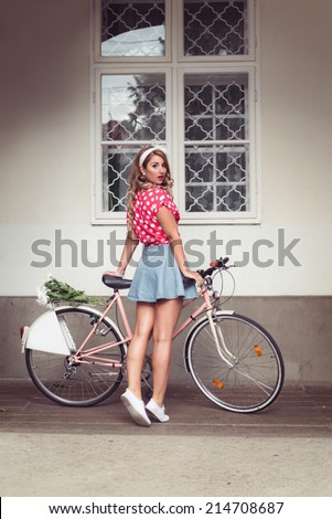 Pin Up Girl posing next to her old retro bicycle, bike, dressed in a very short and sexy denim skirt and red shirt with polka dots. Posing with her back, with nice long legs. Copy space on bike - stock photo