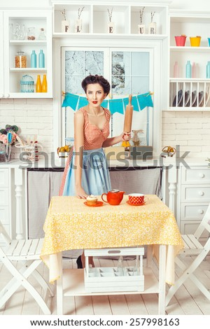 Pin-up girl style. Retro girl standing in the kitchen with a rolling pin for the dough in his hands. - stock photo