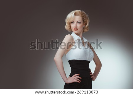 Pin-up girl, 50 style. Studio shot of young and beautiful woman wearing white blouse and black fitting, in studio. Professional makeup and hair style - stock photo