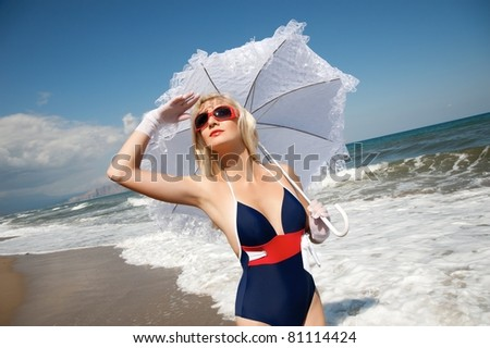 Pin up girl with umbrella on the beach - stock photo