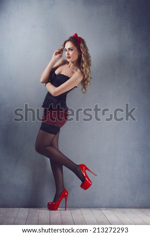 pin up sexy beautiful young blond woman  makeup standing in a corset in a corset and mini skirt black stockings on high heels red shoes cost booty rastavit foot hand toward - stock photo