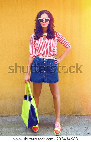 Pin up styled fashion portrait of pretty woman with retro hairstyle cat eye sunglasses and bright vintage clothes, yellow background. - stock photo