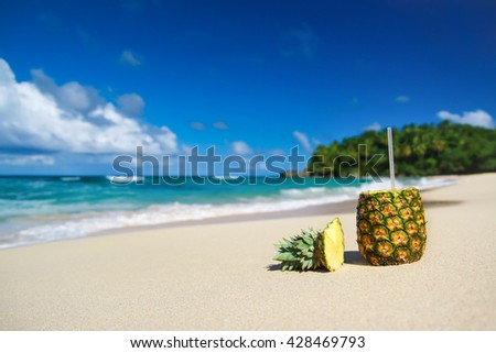 Pina colada cocktail with pipe on beautiful sandy beach - stock photo