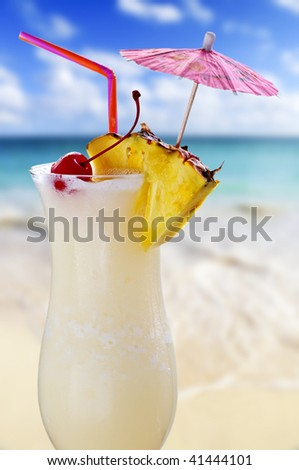 Pina colada drink in cocktail glass with tropical beach in background - stock photo