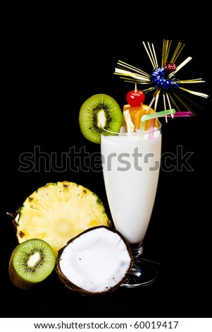 Pina Colada over black background, garnished with slice of pineapple, kiwi and coconut. - stock photo