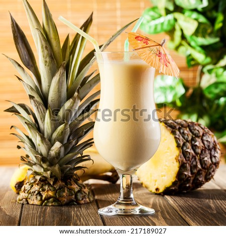 Pina Colada over wooden background garnished pineapple - stock photo