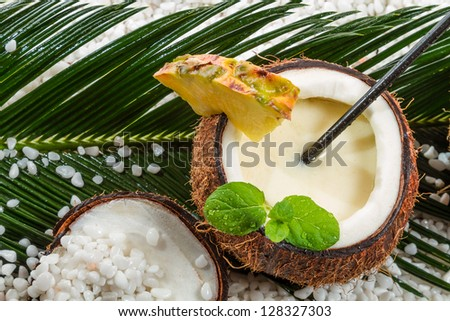 Pinacolada in a coconut on the beach - stock photo