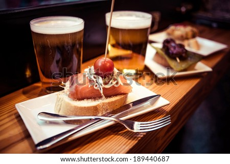 Pinchos or pintxos, traditional Basque Country appetizer. Served with beer - stock photo