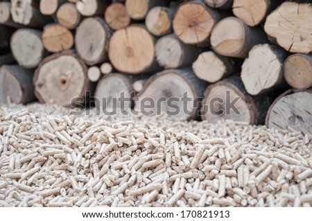 Pine pellets infront apile of fire wood - stock photo