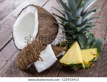 Pineapple and Coconut Pieces on wooden background - stock photo
