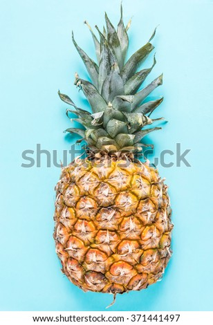 Pineapple  blue pastel background, lay flat overhead view, vibrant colors - stock photo