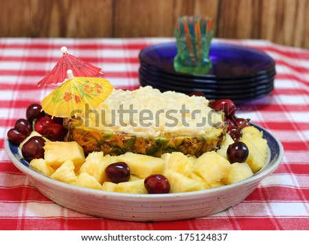 Pineapple dip in half a pineapple surrounded with fresh pineapple and cherries. - stock photo