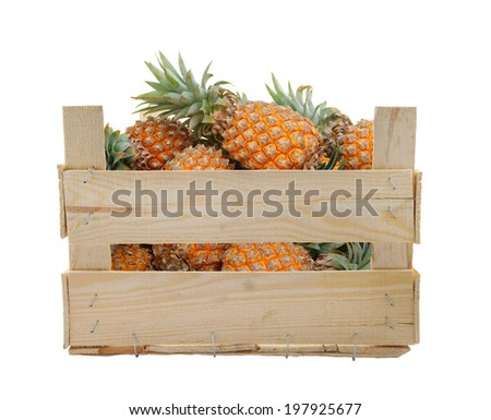 Pineapple fruits in wooden box isolated on white background - stock photo