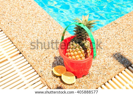 pineapple in toy bucket with beach toys at swimming pool. - stock photo