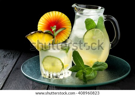 Pineapple lemonade with lime, mint and ice in a pitcher and glass on a glass tray  - stock photo