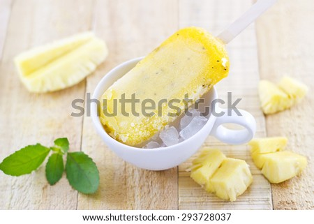 Pineapple popsicles homemade in ice cup and mint on wooden background, soft focus - stock photo
