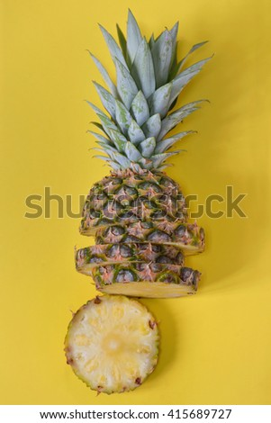 Pineapple slices isolated on yellow background - stock photo