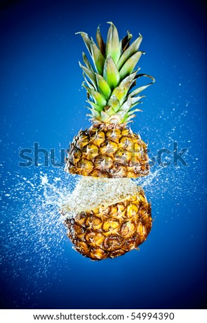 Pineapple splashed with water on a blue background - stock photo