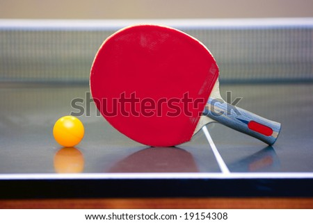 Ping pong ball and racket lying in the corner of the table - stock photo