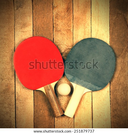 Ping pong paddles and ball on vintage wooden background - stock photo