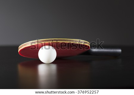 ping pong racket and ball on dark table - stock photo