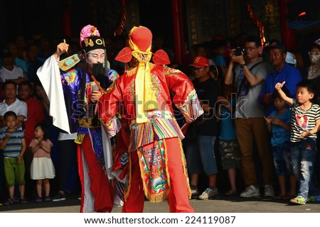 PINGTUNG,TAIWAN - October 15 : Donggang King boat ceremony folk arts troupes on October 15, 2014 in Pingtung,TW. Eight Generals civil and military judge show, kid raised his hand and said Zambia - stock photo