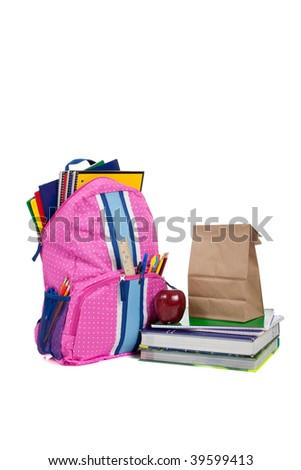 Pink and blue backpack with school supplies, textbooks, an apple and a sack lunch - stock photo