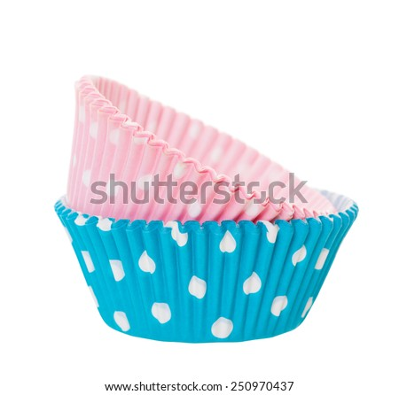Pink and blue cupcake wrappers with white polka-dots on a white background.  Boy and girl theme. - stock photo