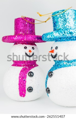 Pink and blue snowmans on white background - stock photo