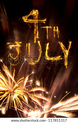 Pink and gold fireworks display with 4th July written in sparklers - stock photo
