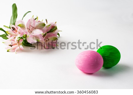Pink and green Easter eggs with floral design and pink flowers on a white background. Easter background. Easter background. Easter symbol. Copy space - stock photo