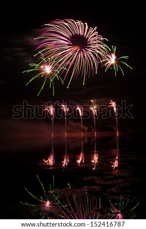 Pink and Green Fireworks reflected in a murky lake - stock photo