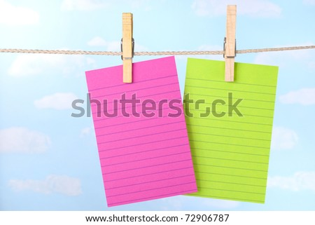 Pink and green paper note cards pinned to clothesline with a blue sky background - stock photo