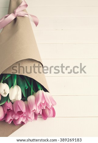 Pink and hot pink tulips wrapped in a white wood table with copy space - stock photo