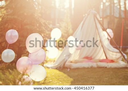 pink and white baloons at sundet near wigwam - stock photo