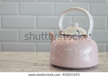 Pink and White Stovetop whistling kettle on table. - stock photo