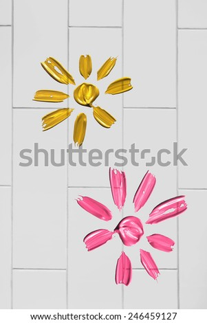 Pink and yellow painted flowers on white brick wall - stock photo