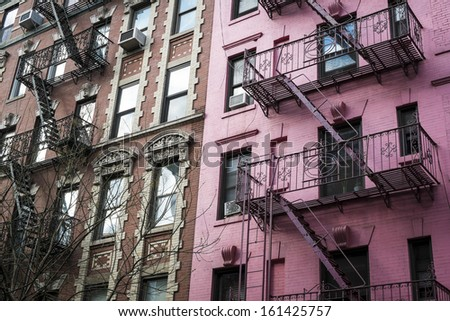 Pink apartment building with fire escapes, New York City - stock photo