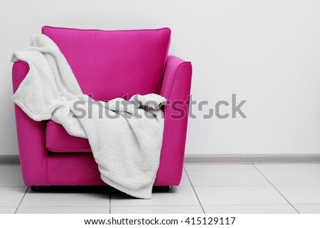 Pink armchair with blanket on light wall background - stock photo