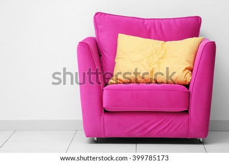 Pink armchair with yellow pillow on white wall background - stock photo