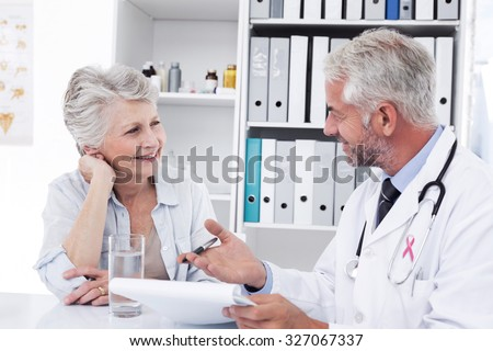 Pink awareness ribbon against female senior patient visiting a doctor - stock photo