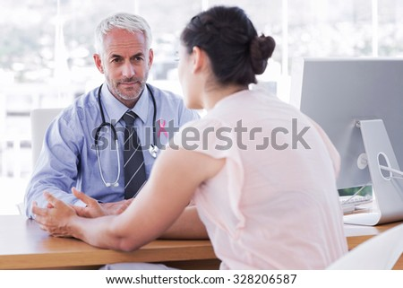 Pink awareness ribbon against patient explaining her painful to doctor - stock photo