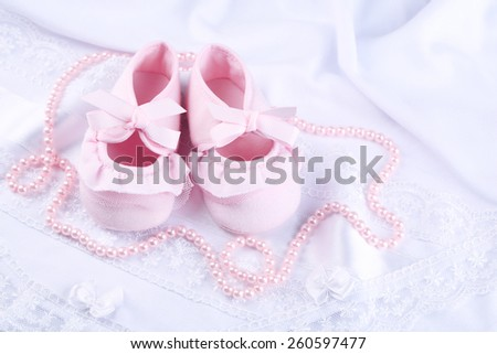 Pink baby boots on cloth close-up - stock photo