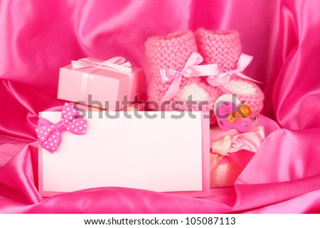 pink baby boots, pacifier, postcard and gifts on silk background - stock photo